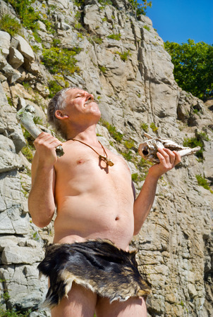 The man in loin-cloth stands at rocks with skull and bone in his hands. photo