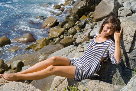 striped vest: The young woman in old striped vest lies on rock at sea. Stock Photo