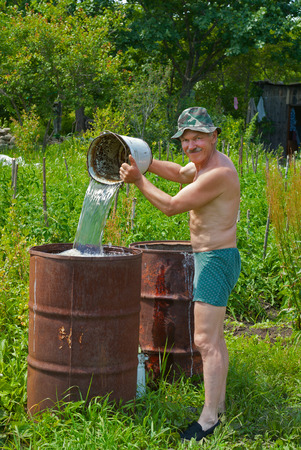 The gardener pours water into a barrel with bucket. photo
