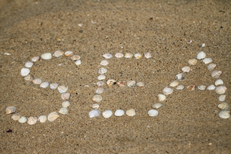Letters made ​​of shells on the sand photo