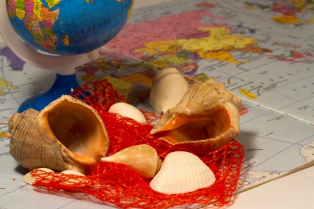 exotism: Seashells and small globe on a book with a geographical map  Stock Photo