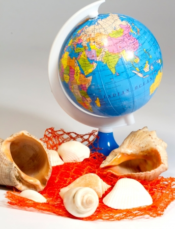 Seashells and small globe on a book with a geographical map  Stock Photo