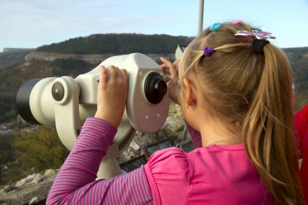 distant spot: Girl looks into the distance through a telescope