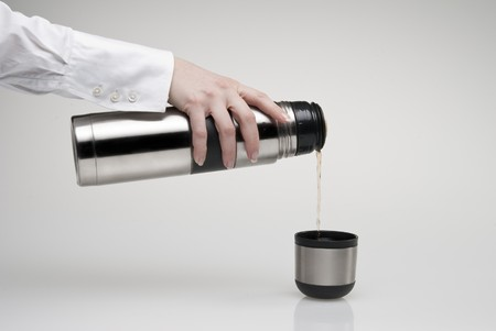 Female hand pouring tea from thermos photo