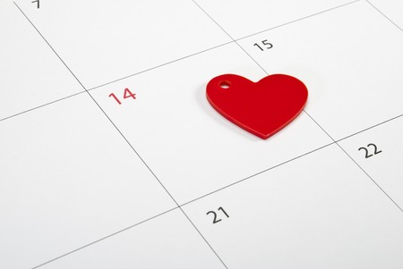 Red heart sign laying on calendar page points St. Valentines day Stock Photo