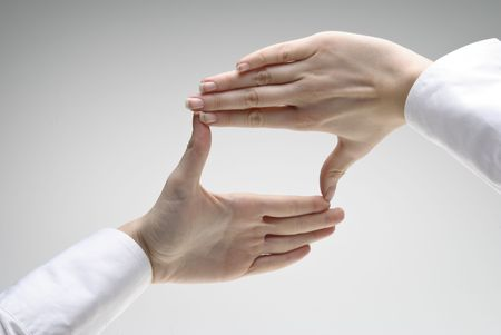 Womans hand showing crop symbol over light background
