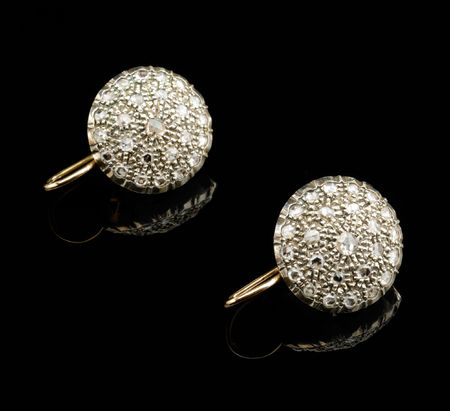 Two golden earrings with diamonds over black background