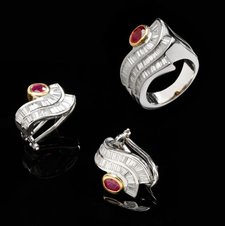 Two silver earrings and ruby ring over black background Stock Photo