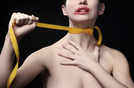 smother: Young woman throttle herself by tape-line. Black background