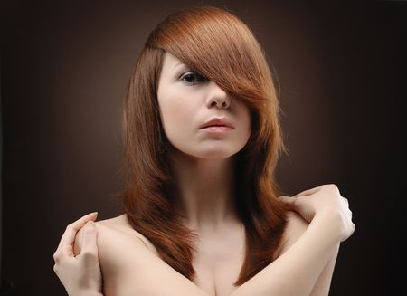 Portrait of young beautiful woman folding arms round her shoulders