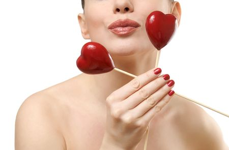 Beautiful woman holding two red hearts. Face closeup kissing. Isolated on white background Stock Photo