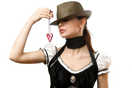 Young woman wearing hat showing heart shaped pendent. Isolated on white background