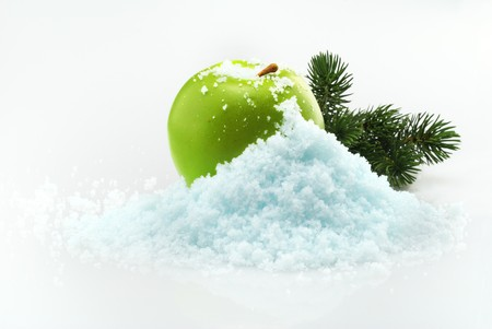Green delicious Christmas apple in snow with christmas tree branches on the background Stock Photo