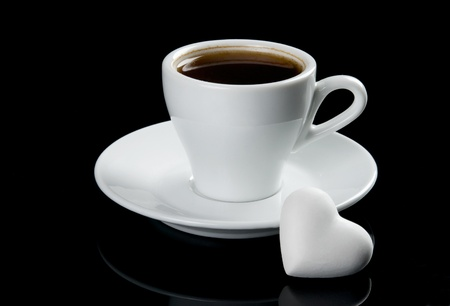 Cup of coffee with heart shape cookie. Isolated on black background photo