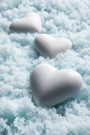 Blank white Hearts on Snow Background. Small Depth of Field. Blue tinted Stock Photo
