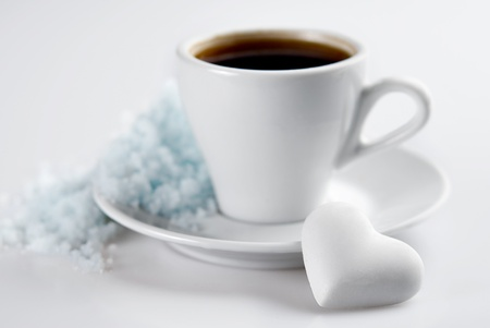 Cup of coffee with heart shaped blank candy and snow hill on saucer. Isolated on white. Small Depth of Field photo
