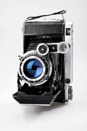 Old vintage photo camera isolated on white background