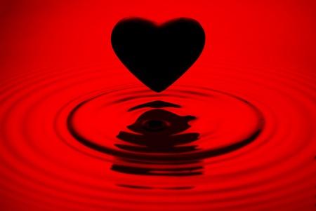 Black heart siluett over red water ripples background Stock Photo