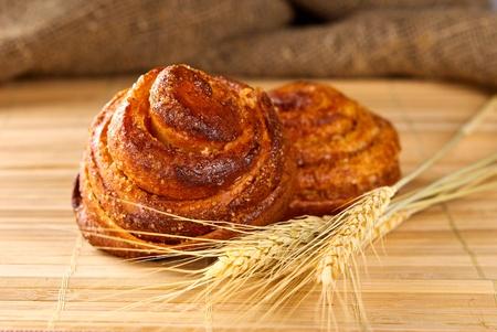 Cinnamon rolls with ear of wheat closeup Stock Photo