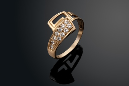 Golden ring with diamonds over black background photo