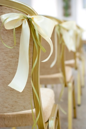 Empty wedding chairs elegantly decorated with bow