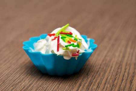 Portion of whipped cream in a blue form over wooden background. Shallow DOF photo