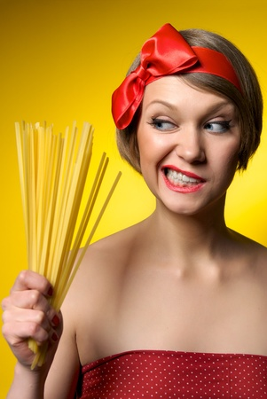 Portrait of young housewife holding pasta in her hand. Retro styled. Isolated on yellow background