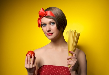 Portrait of young housewife holding potato and pasta in her hands. Retro styled. Isolated on yellow background