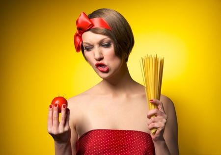 Portrait of young housewife holding potato and pasta in her hands. Retro styled. Isolated on yellow background photo