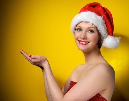 Pretty christmas girl wearing red dress and santa hat, smiling. Isolated on yellow background photo