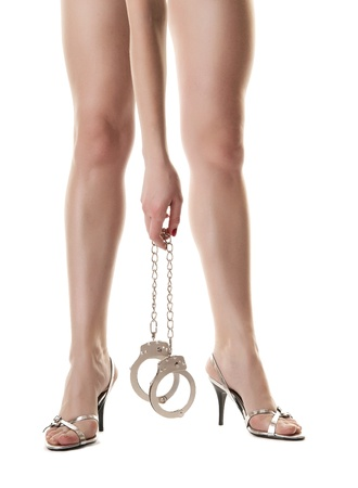 A pair of long female legs and hand holding handcuffs. Isolated on white background Stock Photo - 9507701