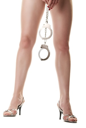 A pair of long female legs and hand holding handcuffs. Isolated on white background Stock Photo - 9507709