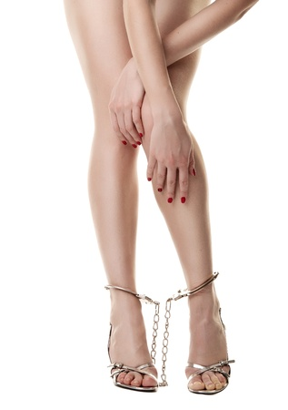A pair of long handcuffed female legs isolated on white background Stock Photo - 9507708