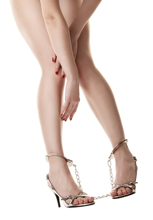 A pair of long handcuffed female legs isolated on white background Stock Photo - 9507711
