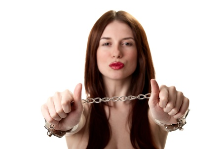 Young sexy brunette in handcuffs isolated on white background Stock Photo