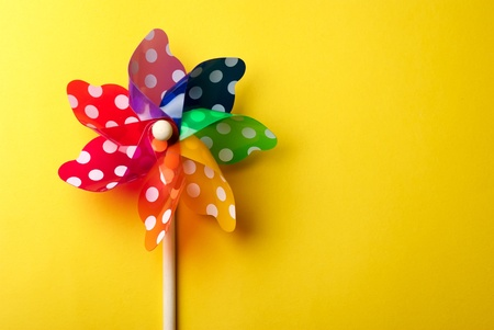 whirligig: Childrens colorful windmill toy isolated on yellow background Stock Photo