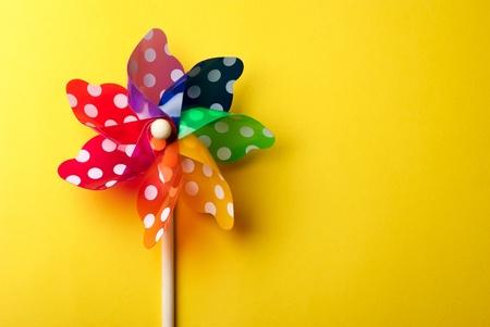 vibrant colors fun: Giocattolo di mulino a vento colorato per bambini isolato su sfondo giallo