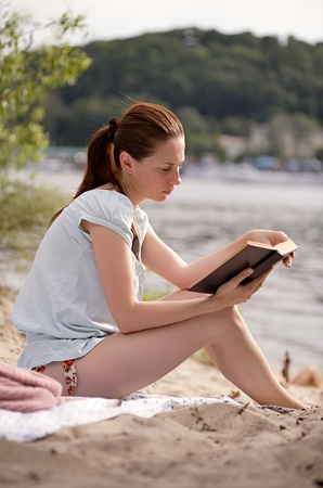 dniper: Young girl sitting on the riverside reading the book