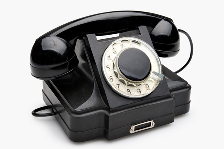 Old black vintage rotary style telephone isolated over a white background