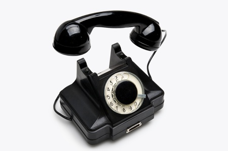 Old black vintage rotary style telephone isolated over a white background photo