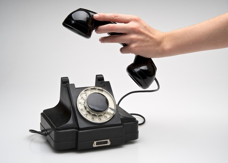 hangs: woman hand hanging up the handset of an old black telephone isolated ocer white background