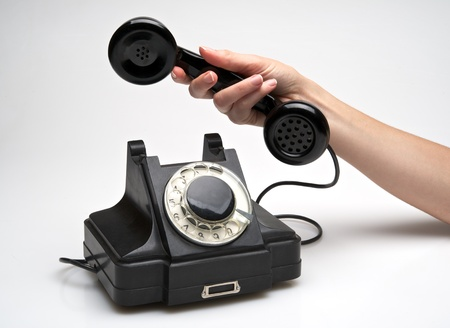rotary dial telephone: woman hand hanging up the handset of an old black telephone isolated ocer white background