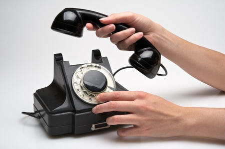 woman hand hanging up the handset of an old black telephone isolated ocer white background