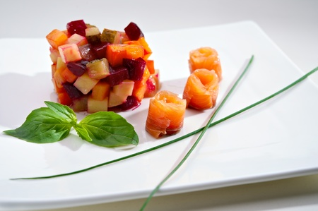 Appetizer of Vinaigrette salad with boiled vegetables and salmon fillet. Small Depth of Field