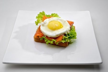 Fish breakfast with scrambled eggs and smoked salmon on toast, served on white plate photo