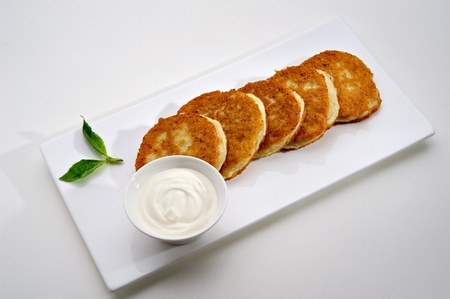 Potato pancakes served on white plate with sour cream photo