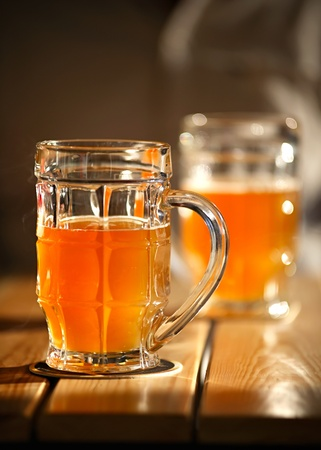 Two beer mugs close-up on wooden table. Small depth of field photo