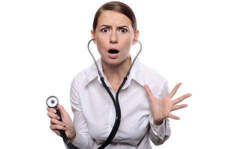 frightened: Doctor shocked - funny. Portrait of young female doctor or nurse surprised starring with big eyes. Isolated on white Stock Photo