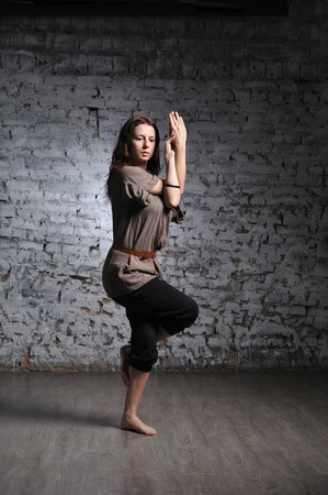 Full-length portrait of young beautiful woman doing yoga excercise against a brick wall photo