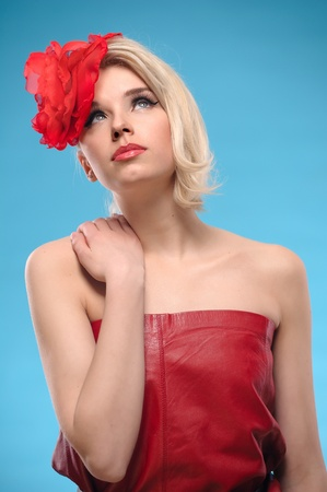 Portrait of beautiful blond woman with a red flower in her hair on a blue background photo
